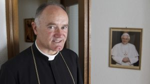 Bishop Bernard Fellay, superior of the Society of St. Pius X, is pictured in 2012 near a photo of Pope Benedict XVI at the society's headquarters in Menzingen, Switzerland. Pope Benedict, who tried to reconcile with the society, said he no longer has the energy to exercise his ministry over the universal church and will resign at the end of the month. (CNS photo/Paul Haring) (Feb. 11, 2013) See BENEDICT-BIO Feb. 11, 2013.