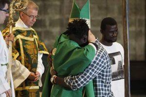 Luis Argüello abraza a un inmigrante al recibir la Cruz de Lampedusa